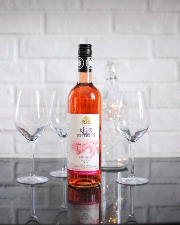 Vins du Québec | Bouteille de vin rosé du vignoble la Halte des Pèlerins avec coupes et mur de briques blanc
